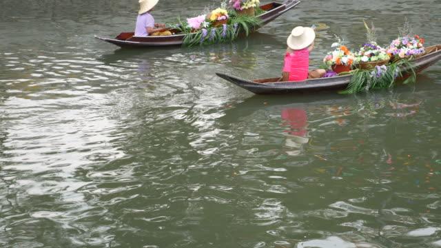 yüzen pazarda çiçekler ile tekneler, tayland - pazarcı stok videoları ve detay görüntü çekimi