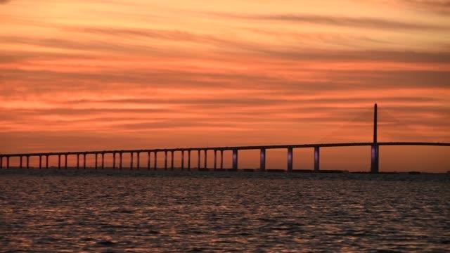 Bob Graham Sunshine Skyway Bridge over the Lower Tampa Bay at sunrise, Florida Bob Graham Sunshine Skyway Bridge over the Lower Tampa Bay at sunrise, Florida florida us state stock videos & royalty-free footage