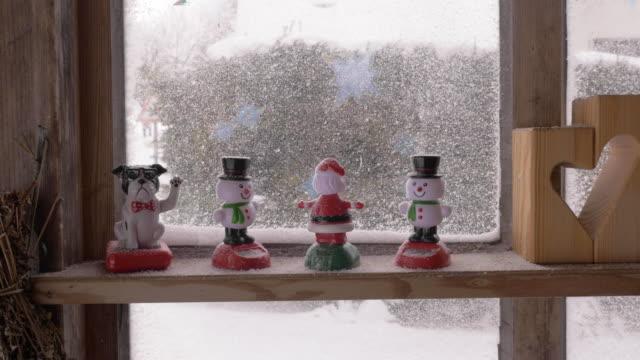 figurine di natale bobbling cosparse di neve artificiale - davanzale video stock e b–roll