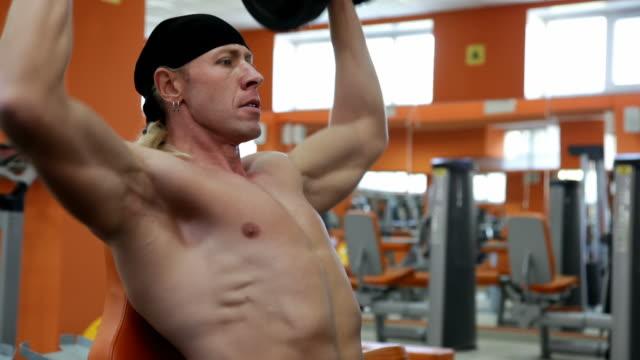 body builder works with pair of dumbbells - bir orta yetişkin erkek sadece stok videoları ve detay görüntü çekimi