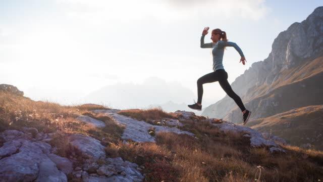 vídeos y material grabado en eventos de stock de cuerpo consciente mujer atleta corriendo al aire libre en la naturaleza en terreno de montaña - terreno extremo
