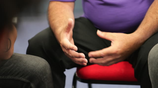 Body Language Close up shot of a mental health professional's hands while he is talking to men in a support group. nhs stock videos & royalty-free footage