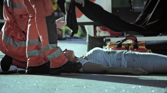body of a young woman being covered with a black sheet at the scene of the car accident - cadavere video stock e b–roll
