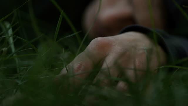 cadavere di morto sdraiato sull'erba, omicidio di gelosia, tasso di banditismo e criminalità - cadavere video stock e b–roll
