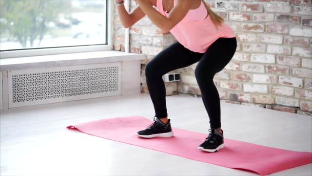 vídeos de stock e filmes b-roll de body of young slim woman, making squats in a hall of fitness club. - agachar se