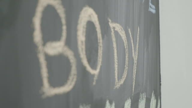 Body powerful strong motivational words written with chalk on a blackboard in a sport gym video