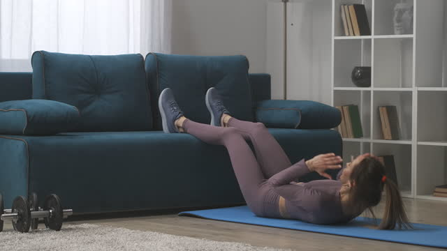 body shaping workout at home, woman is lifting torso for working abdominal muscles lying on floor