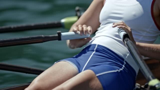 vídeos y material grabado en eventos de stock de fuerza del cuerpo de una atleta femenina, remar en un scull doble en un día soleado - deportes de remo