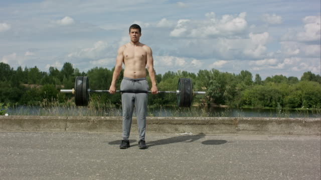 Bodybuilder doing barbell weight workout deadlift with heavy bar video