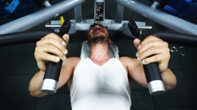 vídeos de stock e filmes b-roll de bodybuilder doing chest exercise at bench press machine - músculo humano