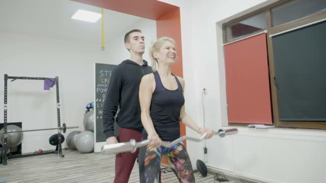bodybuilder weiblich in sportbekleidung workout mit schweren gewichten im fitnessstudio, während ihr persönlicher trainer ihre haltung und übungen korrigiert - sportchampion stock-videos und b-roll-filmmaterial