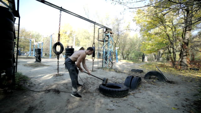 Bodybuilder hits the hammer on the rubber. video