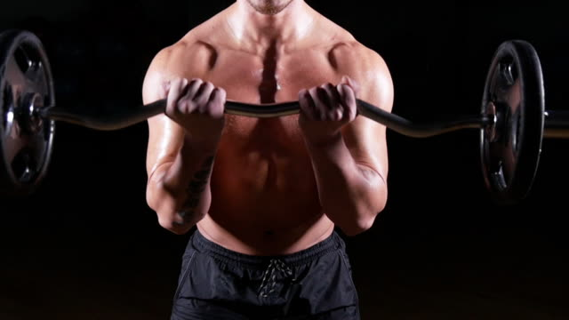 Bodybuilder performing barbell biceps curls video