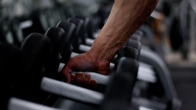 bodybuilder nimmt die hantel. - hantel stock-videos und b-roll-filmmaterial