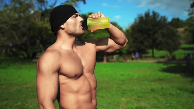 vidéos et rushes de bodybuilder avec l'eau potable parfaite de torse de sa bouteille de sport dans le parc dans le morming tôt. athlète beau se reposant après course de matin. l'homme assoiffé buvant l'eau après le matin efficace s'exerçant à l'extérieur. concept d'en - body building