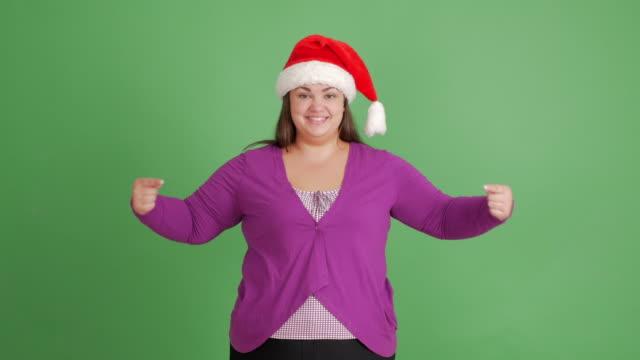 体陽性の女性が。サンタ帽子で脂肪質の女の子は、緑の背景コピー スペースと親指のアップを示しています。 - サンタの帽子点の映像素材/bロール