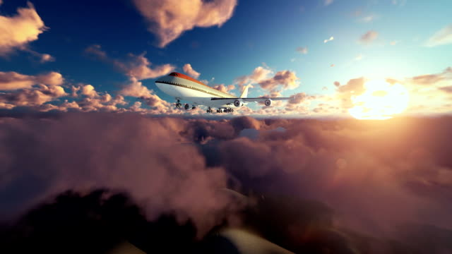 Boeing airplane flying above clouds at sunrise video