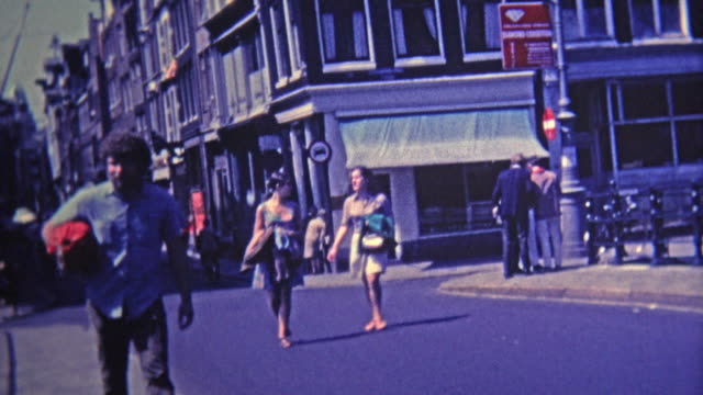 1969: Bohemian district of town people walking and biking narrow streets.