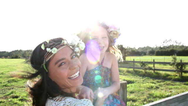 Boho chic woman and little girl on wood fence by pasture video