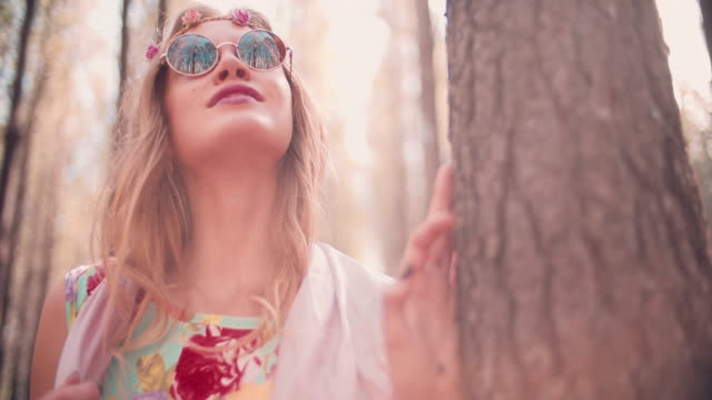 Boho fashion girl with flower headband in a forest video
