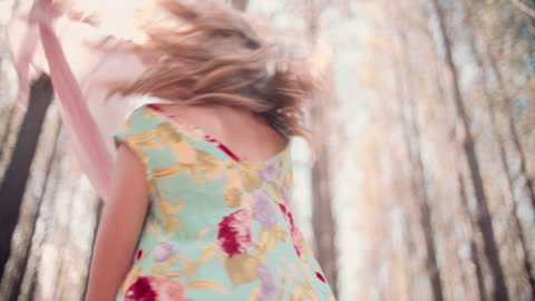 Boho fashion shot in a summer forest with sun flare Low angle boho fashion shot of a girl in a summer forest with sun flare behind her, playing with material  in Slow Motion boho stock videos & royalty-free footage
