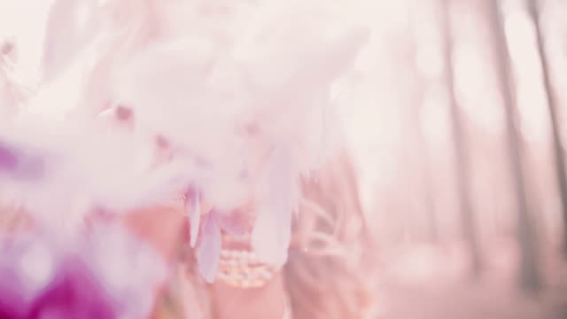 Boho girl blowing brightly coloured pink feathers video