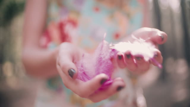 Boho girl holding coloured pink feathers in hand video