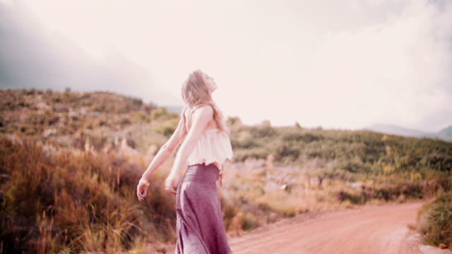 Boho girl on a country dirt road being joyful video