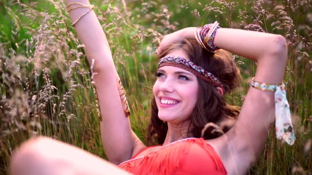 vídeos de stock, filmes e b-roll de boho garota sorridente deitado em um campo de grama selvagem - boho