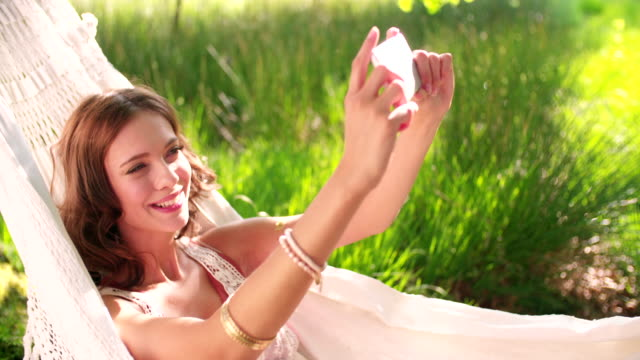 Boho girl taking a selfie on her phone video