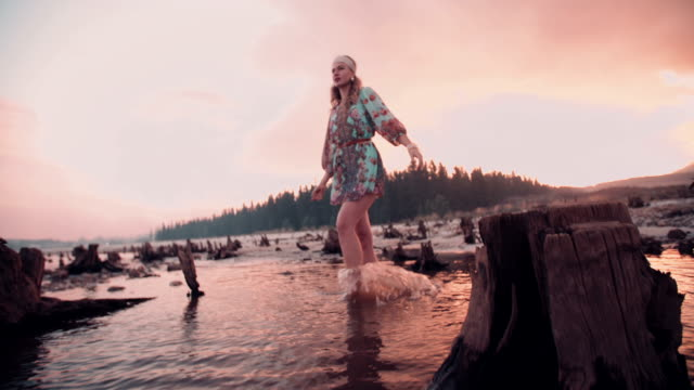 Boho girl walking through a shallow lake at sunset video