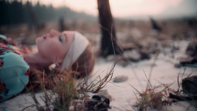 Boho girl with vintage dress and jewellery on sandy ground video
