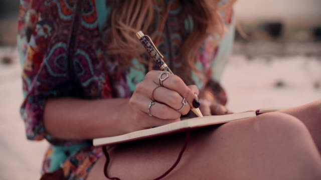 Boho girl writing in her diary wearing a floral dress video