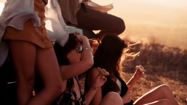 Boho Girls eating pizza outdoor at sunset video