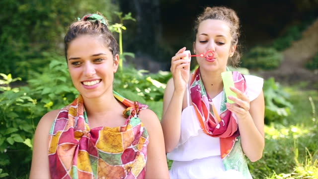 Boho girls surrounded by nature in spring having fun video