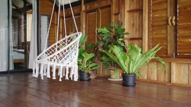 vídeos de stock, filmes e b-roll de cadeira pendurada boho dentro da moderna cabana de madeira - boho