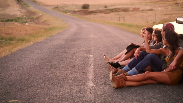 Boho style friends rest leaning against vintage convertible on road video