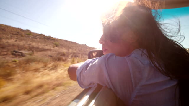 Boho style girl relaxing in convertible during a road trip video