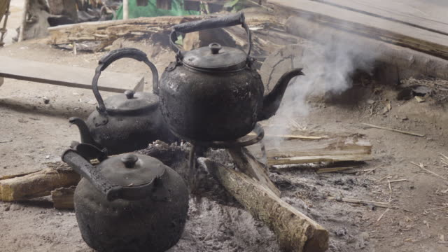 Boil Water Using Black Kettle On Simple Stove With Firewood. - vídeo