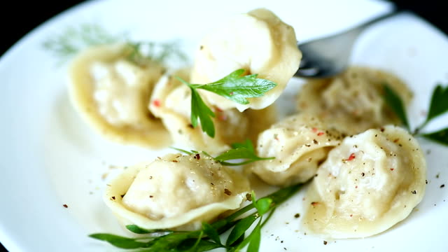 boiled dumplings with meat and spices in a plate boiled dumplings with meat and spices in a plate on a black background ravioli stock videos & royalty-free footage