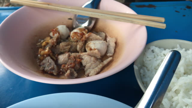 Boiled pork and offal with fried garlic eat with rice and hot soup , Bangkok , Thailand video