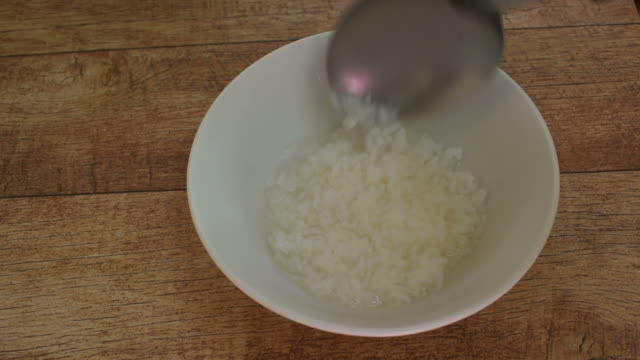 boiled rice scooping in stainless ladle to bowl