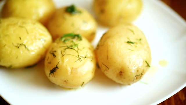 boiled young potato with butter and dill in a plate - молодой картофель стоковые видео и кадры b-roll