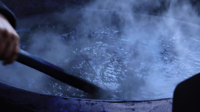 vídeos de stock e filmes b-roll de boiling fabric in the pot to natural tie and dye a procedure to weaving in thailand - matéria corante