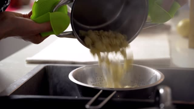 boiling pasta. draining macaroni water through a colander in the sink - pasta video stock e b–roll