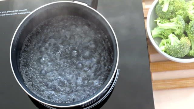 Boiling water at pan on Induction stove top panel for cooking broccoli video