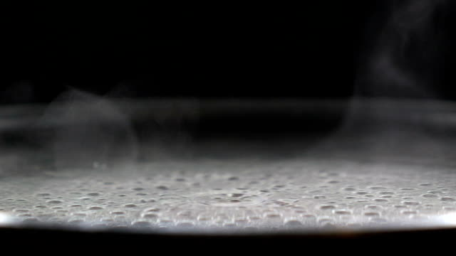 Boiling water bubble and steam over coating pan heating on electronic stove video