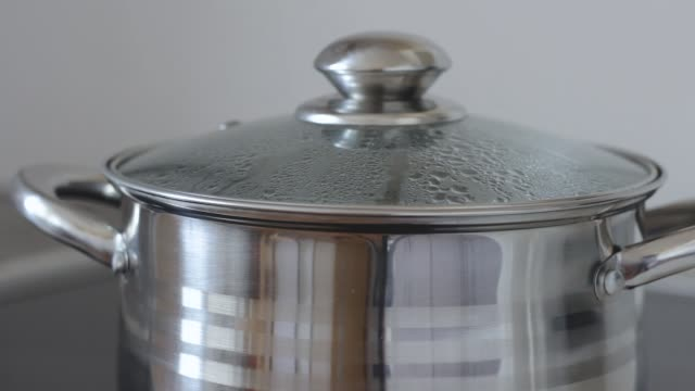 Boiling water in a saucepan with glass lid. Water gurgles, sprinkles and flows from pan