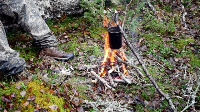 Boiling water in pots above the fire in outdoor video