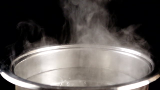 boiling water in steel pan on black background, slow motion - материал стоковые видео и кадры b-roll